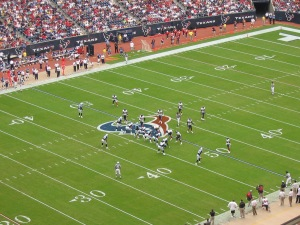 American football game between the Tennessee Titans (in navy blue) and the Houston Texans (in white). Photo Credit: Wikimedia Commons